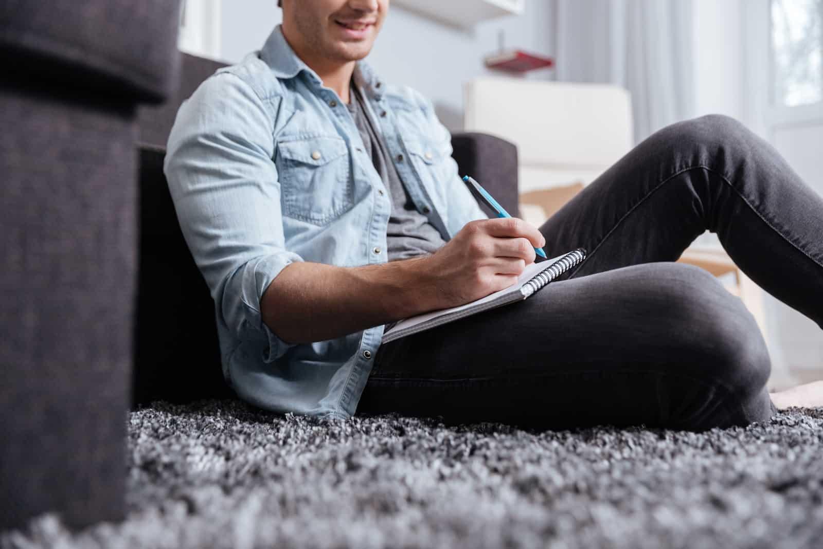 un homme est assis sur le sol et écrit une lettre