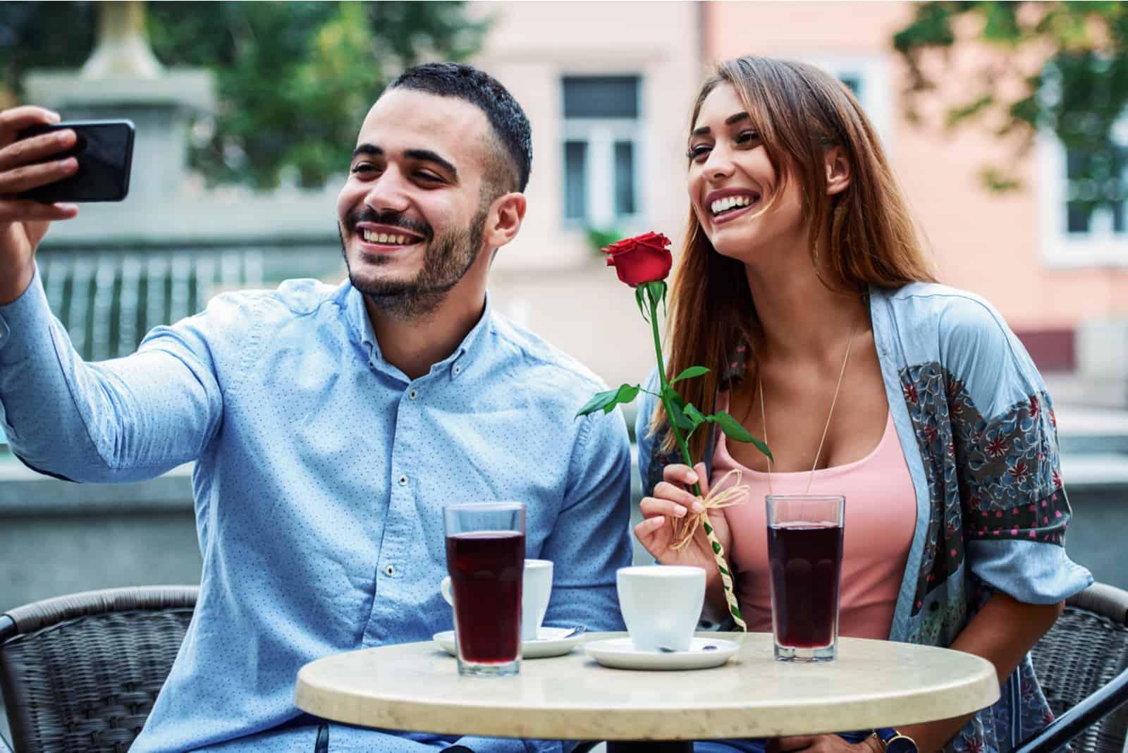 un homme et une femme assis à une table en riant tout en prenant des photos