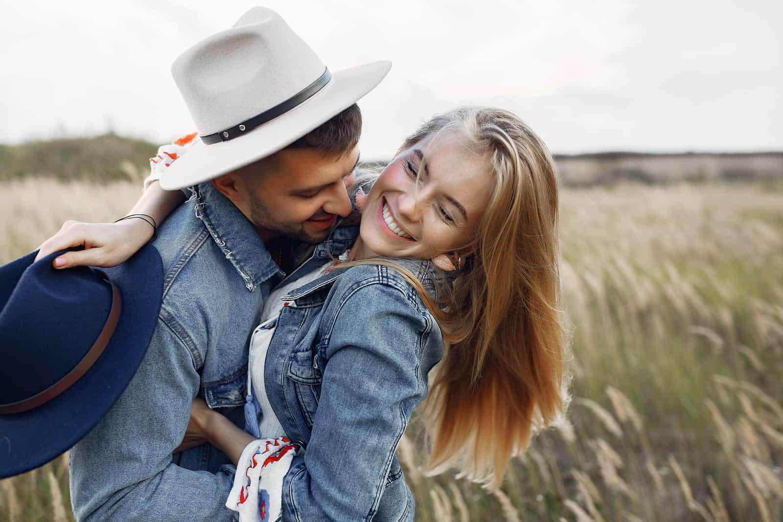 un homme et une femme embrassant dans un champ debout et riant