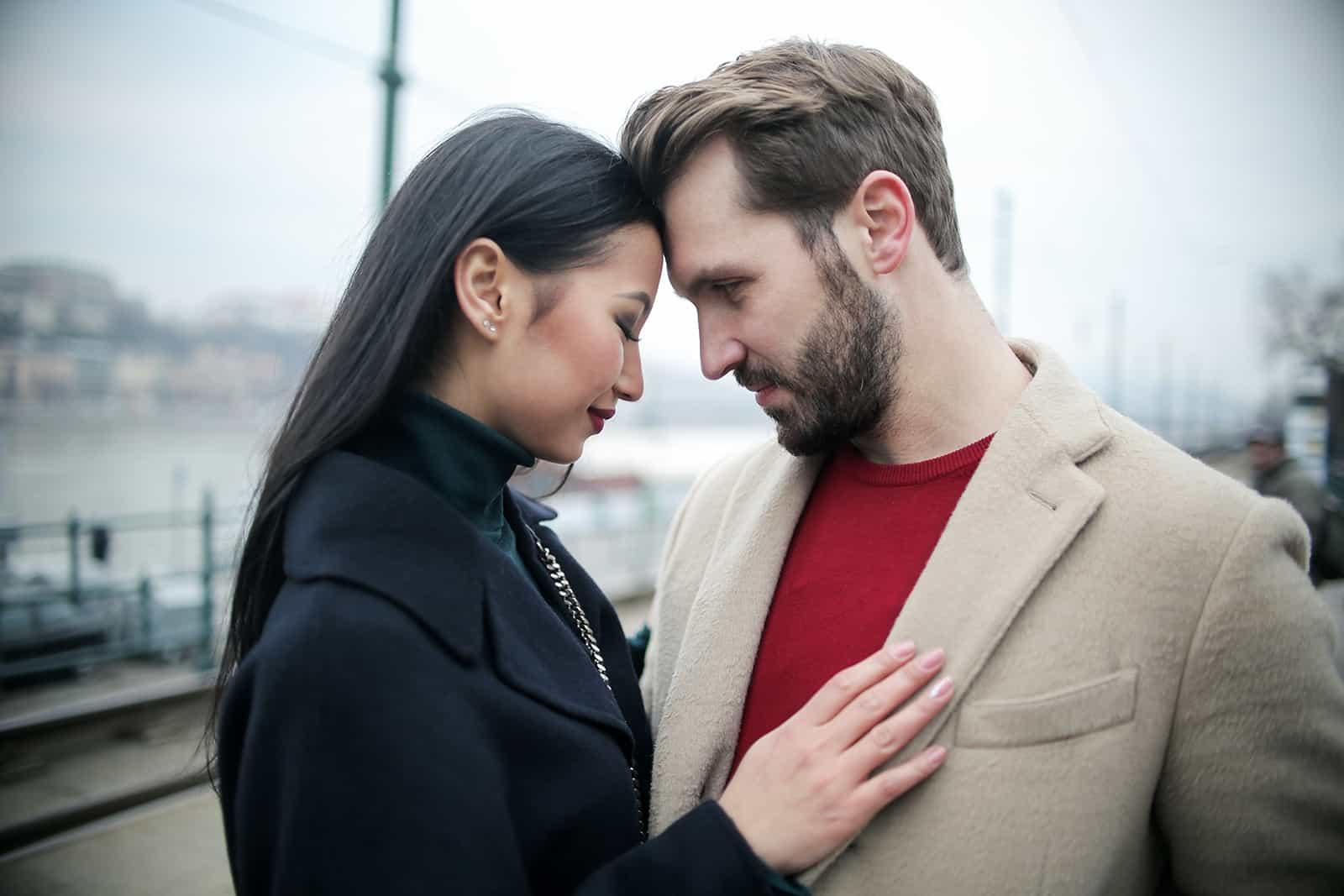 un homme et une femme se serrant dans ses bras debout en plein air