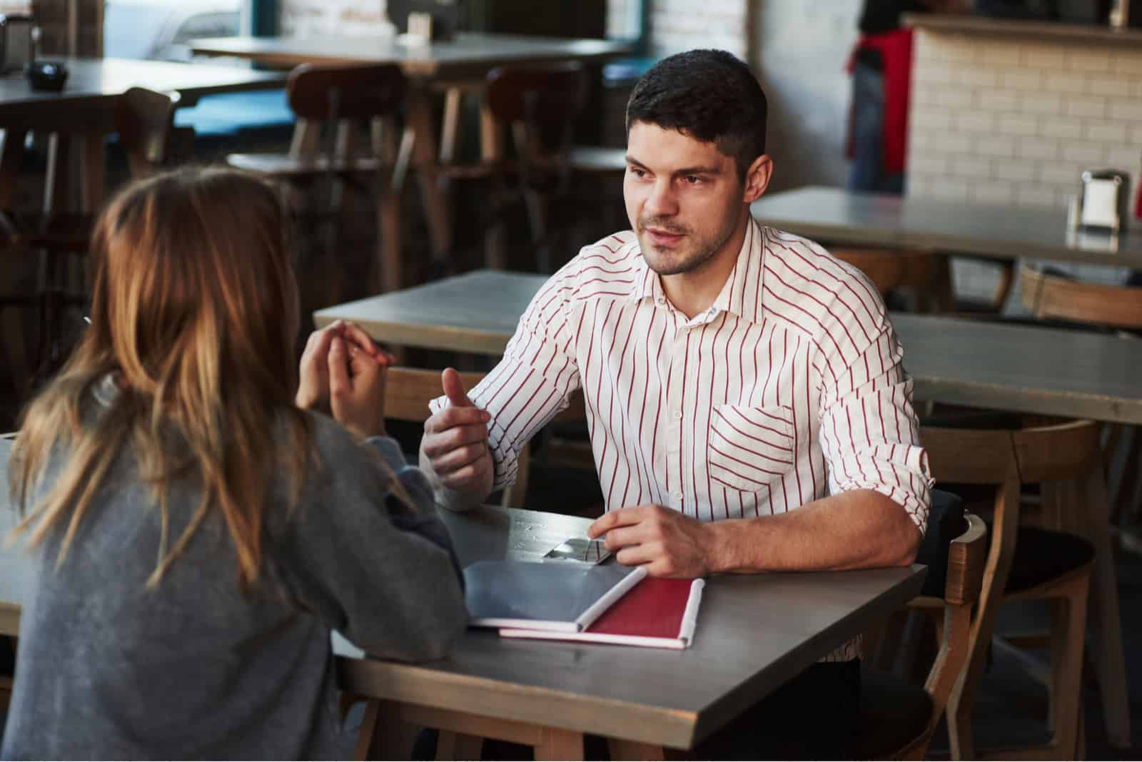 un homme et une femme parlent dans un café alors qu'ils sont assis face à face