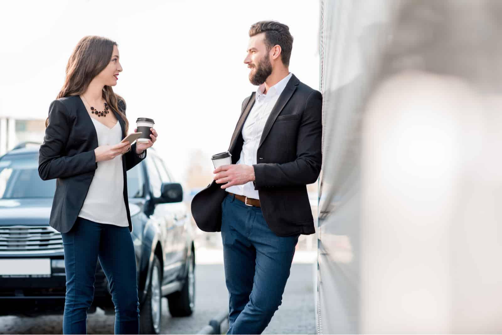 un homme et une femme parlent debout dans la rue, tenant un café à la main