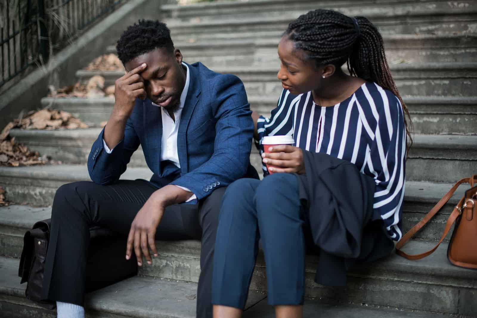 un homme et une femme s'assoient dans les escaliers pendant qu'elle le réconforte