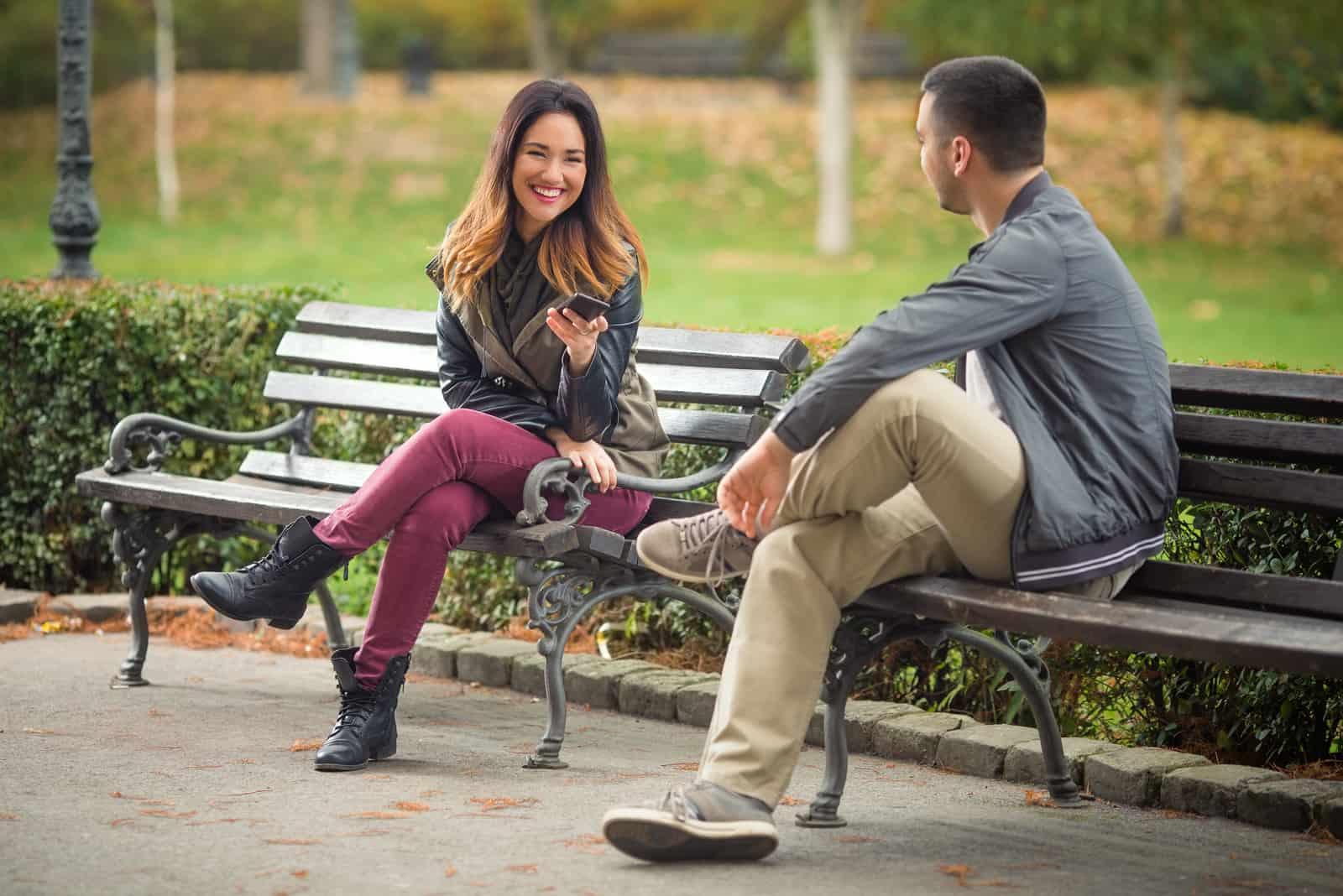 un homme et une femme s'assoient sur un banc de parc et parlent