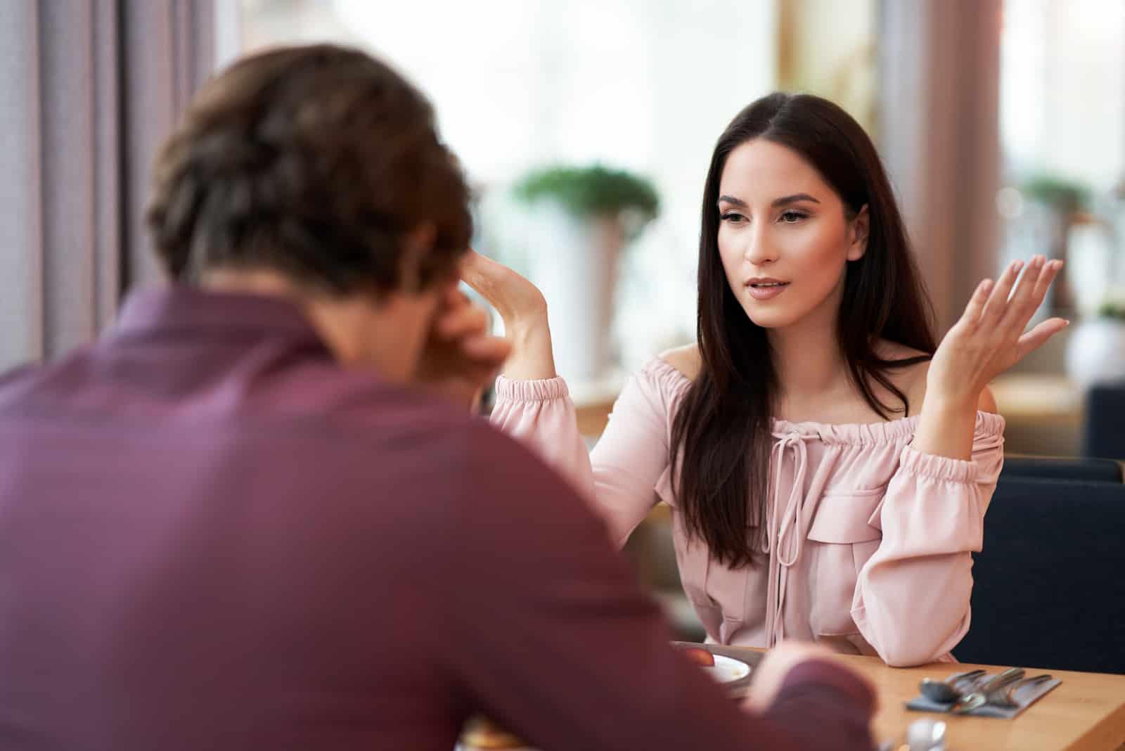 un homme et une femme se disputent dans un café alors qu'ils sont assis face à face
