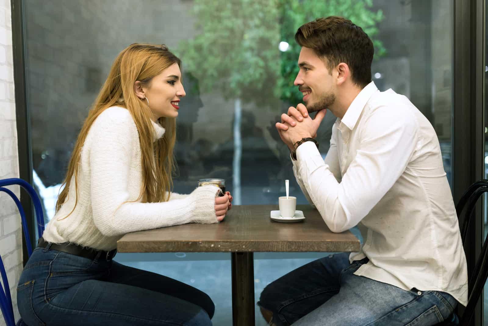 un homme et une femme sont assis à une table face à face