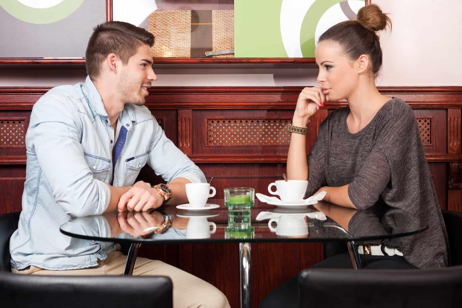 un homme et une femme sont assis dans un café en train de boire du café et de parler