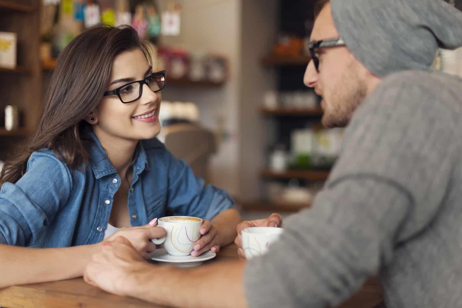 un homme femme dans un café assis et buvant du café