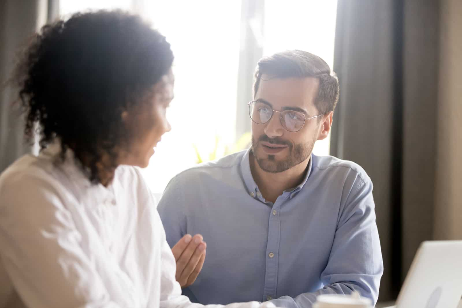 un homme parle à une femme tout en lui expliquant quelque chose