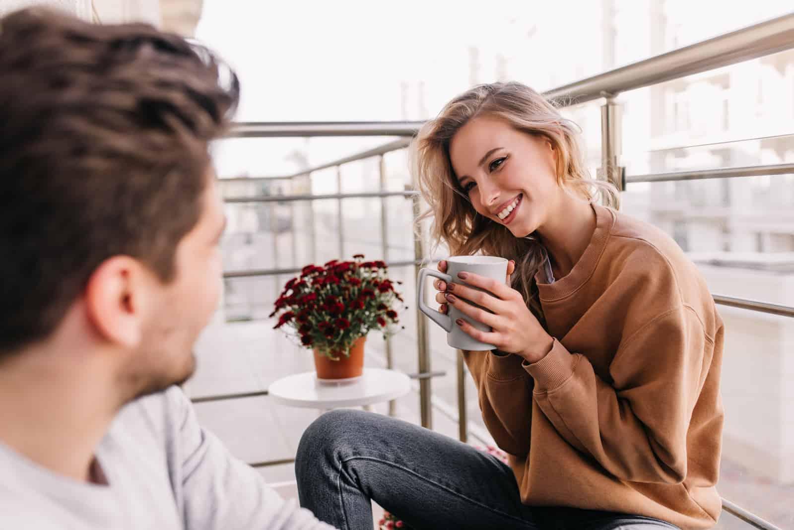 un homme souriant et une femme assise sur le balcon, boire du café et parler
