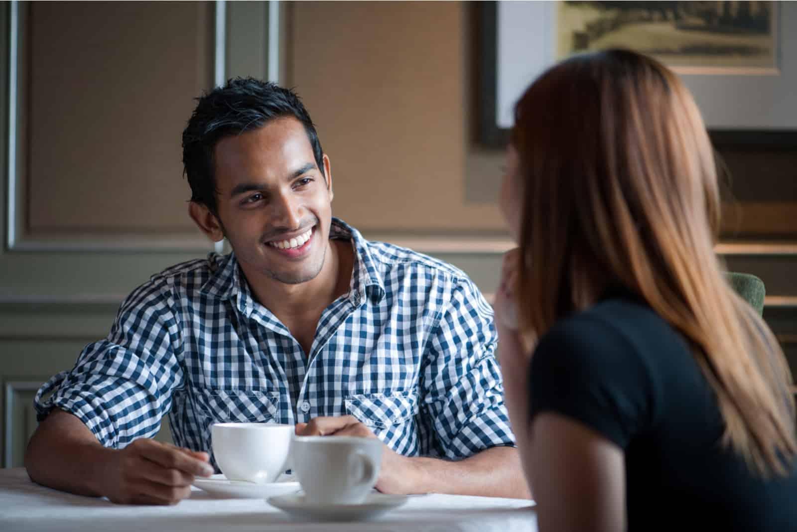 un homme souriant et une femme parlant au café