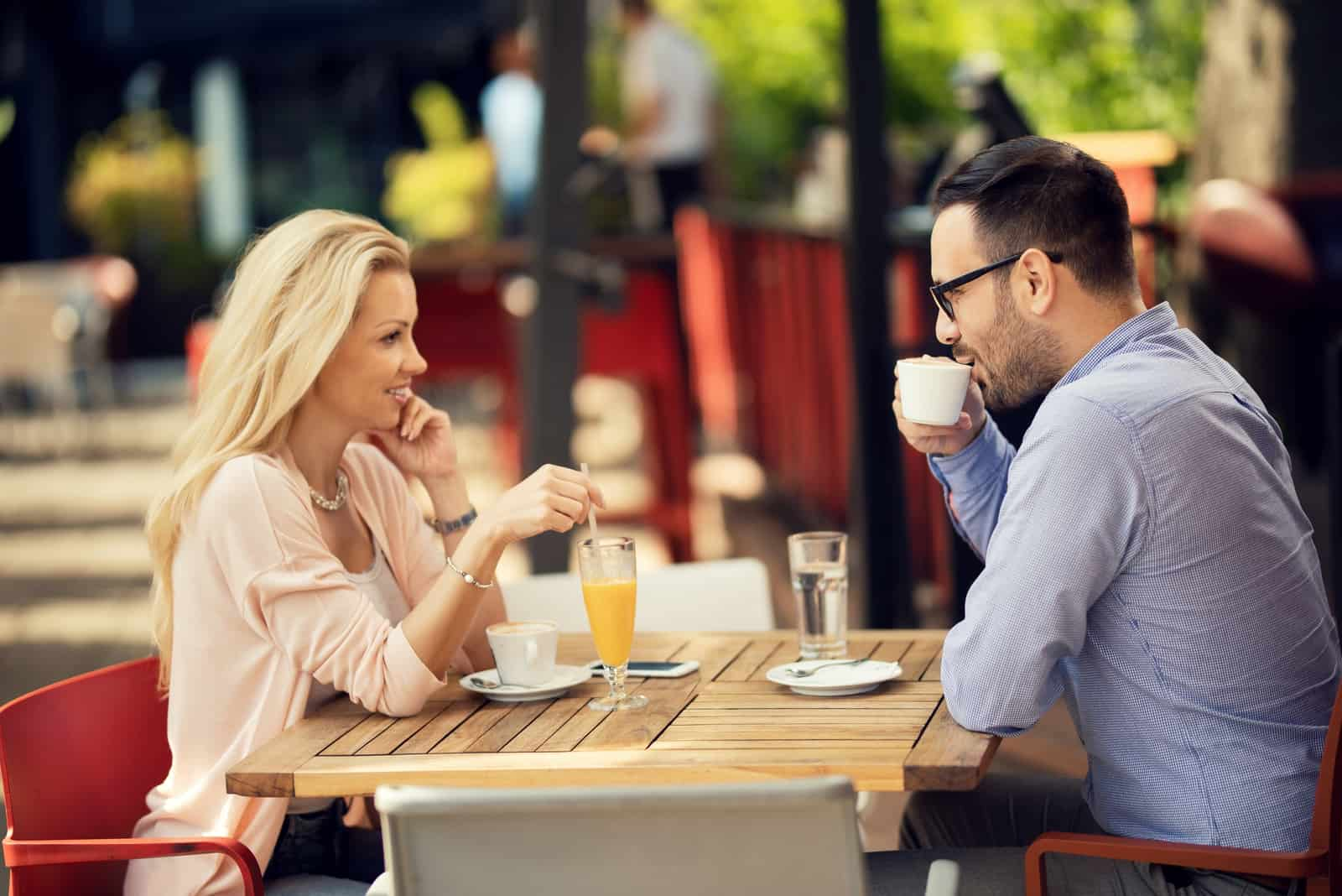 un homme souriant et une femme s'asseoir et boire du café
