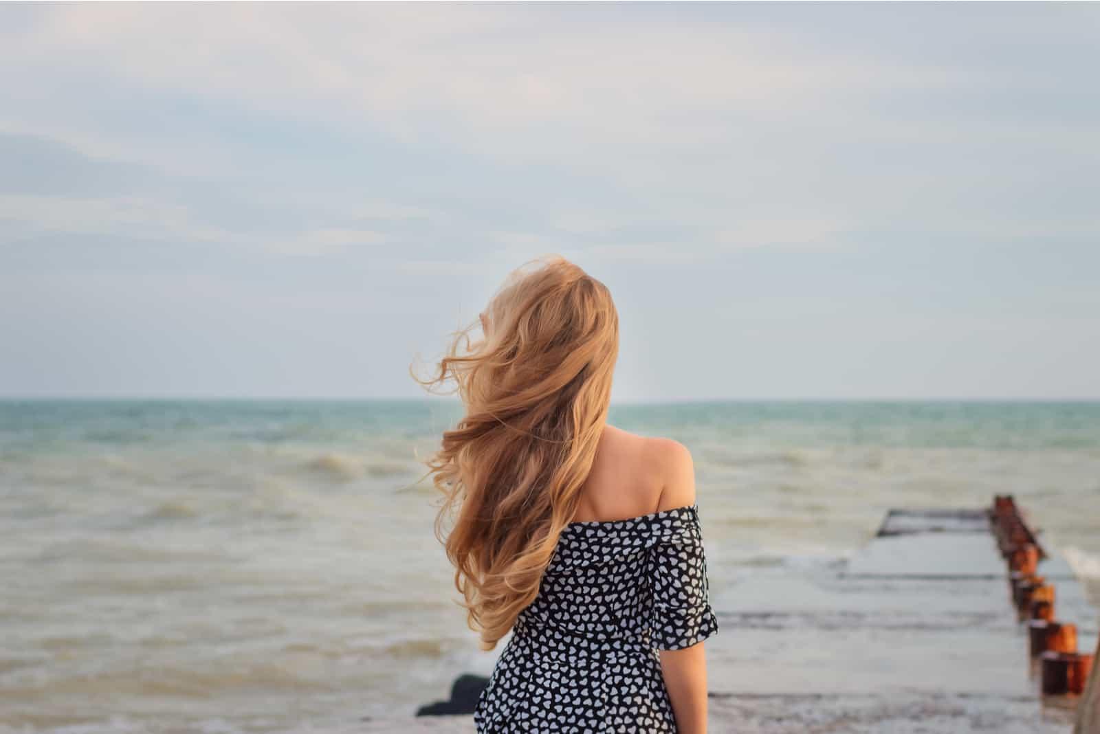 une belle femme aux longs cheveux bruns se dresse au bord de la mer