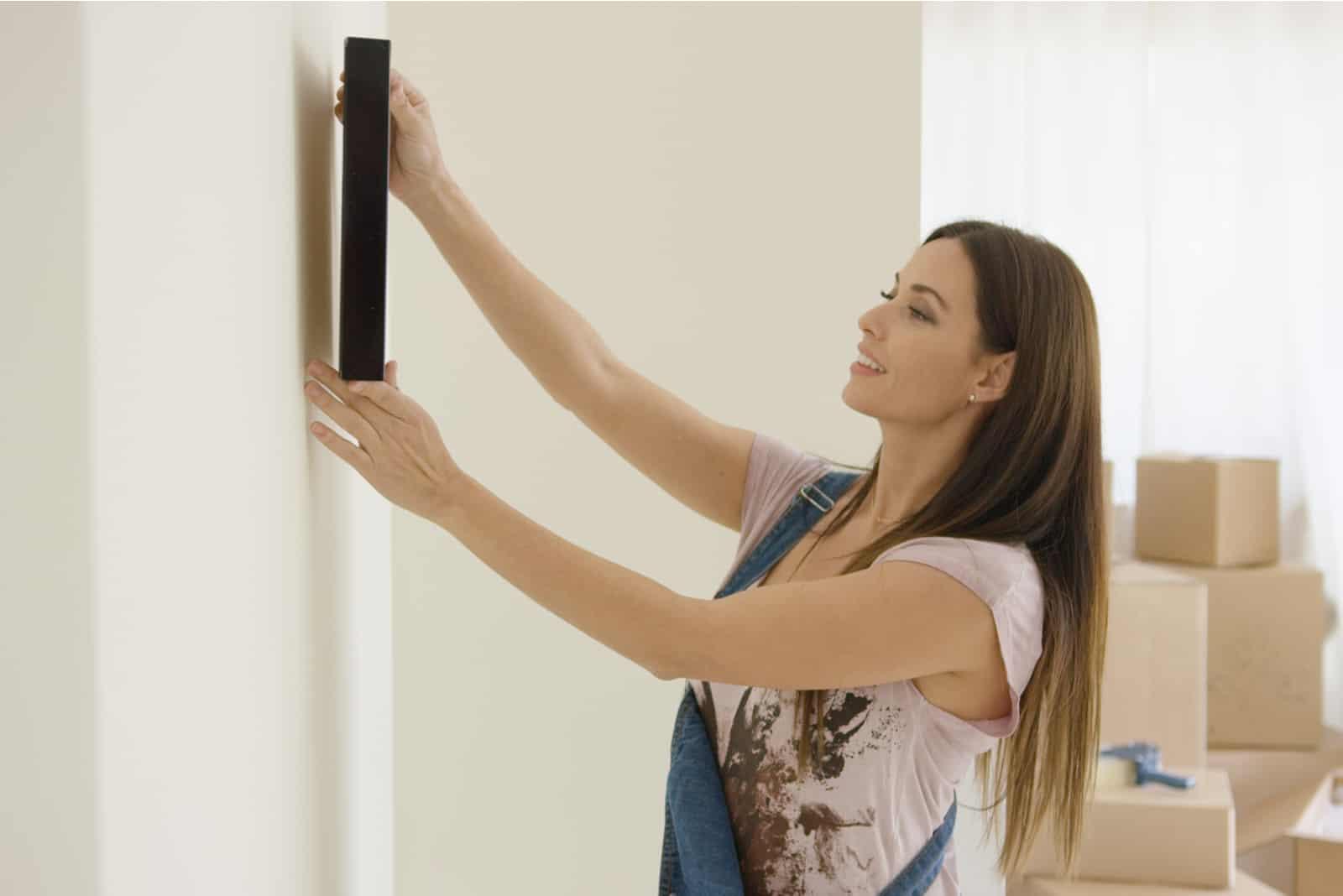 une femme accroche une photo au mur