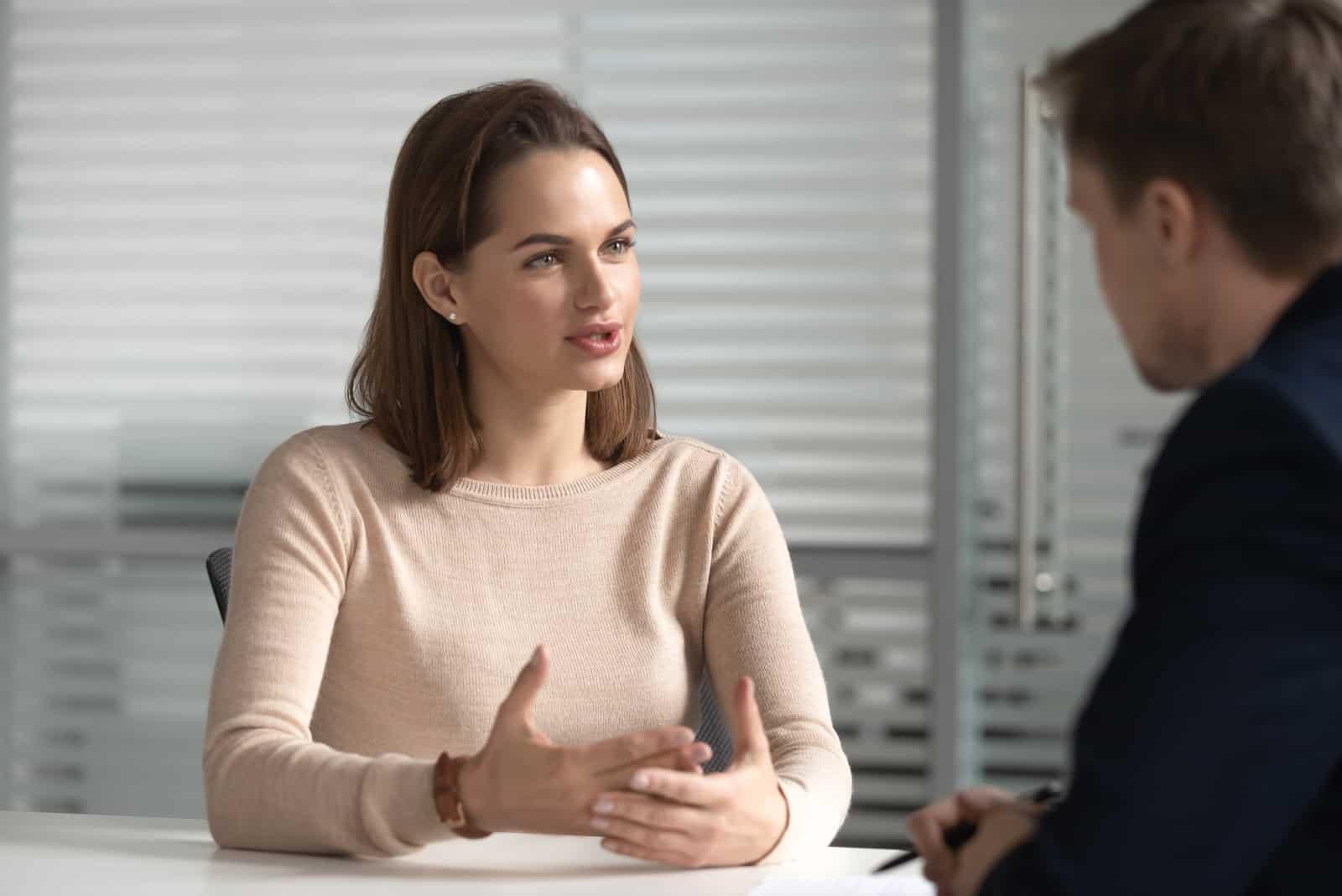 une femme aux cheveux bruns courts parle à un homme