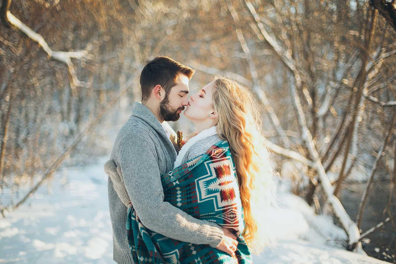 une femme embrassant son homme dans un nez tout en serrant et debout sur une neige