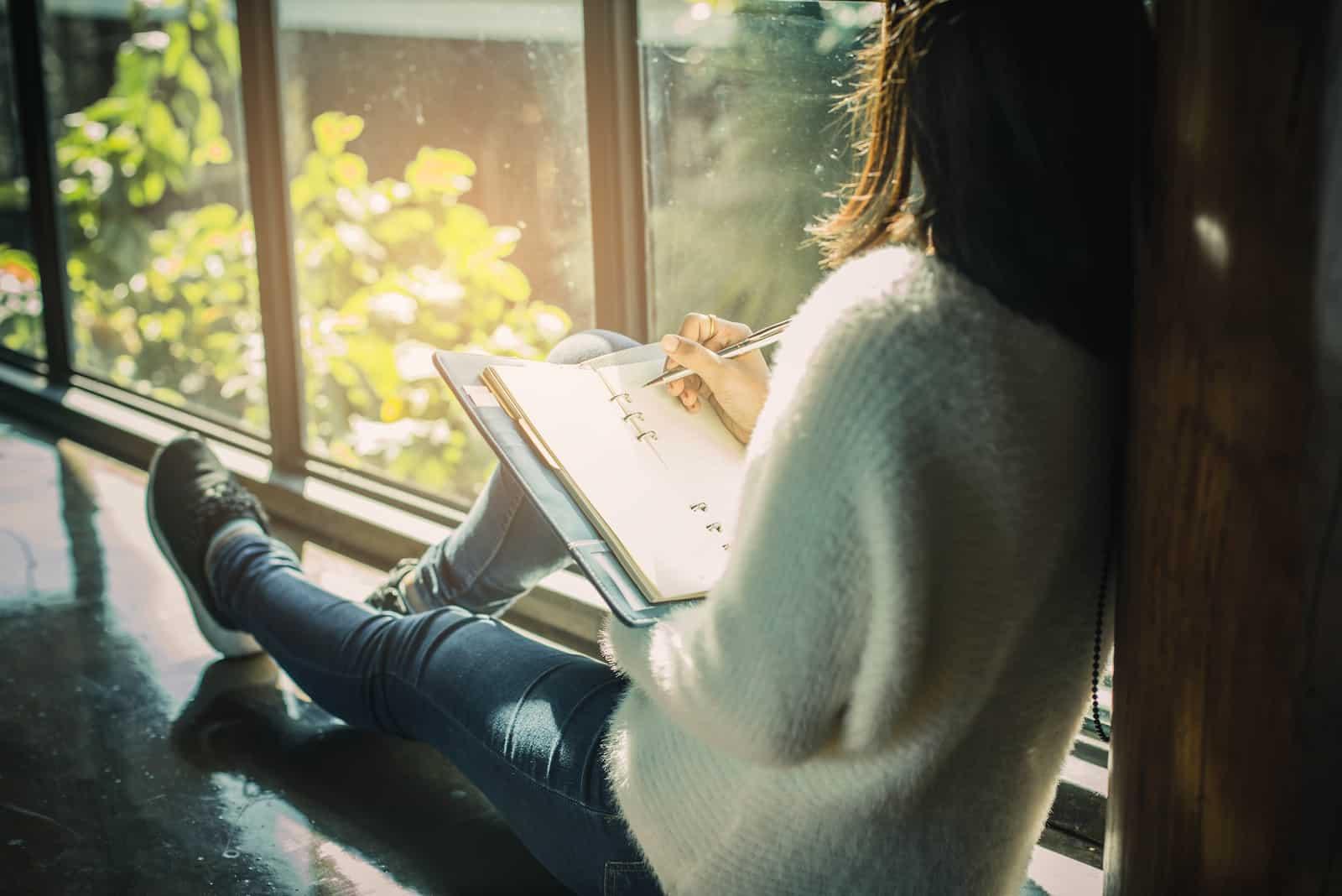 une femme est assise près de la fenêtre et écrit