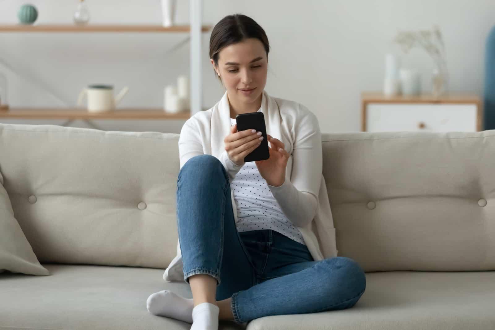 une femme est assise sur le canapé et un bouton sur le téléphone