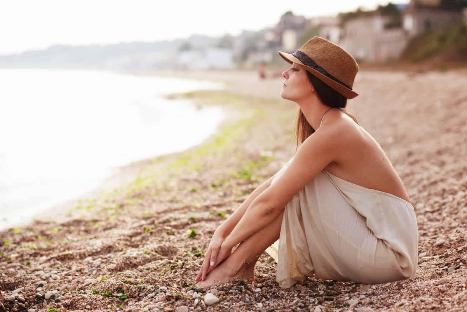 une femme imaginaire avec un chapeau sur la tête est assise sur la plage
