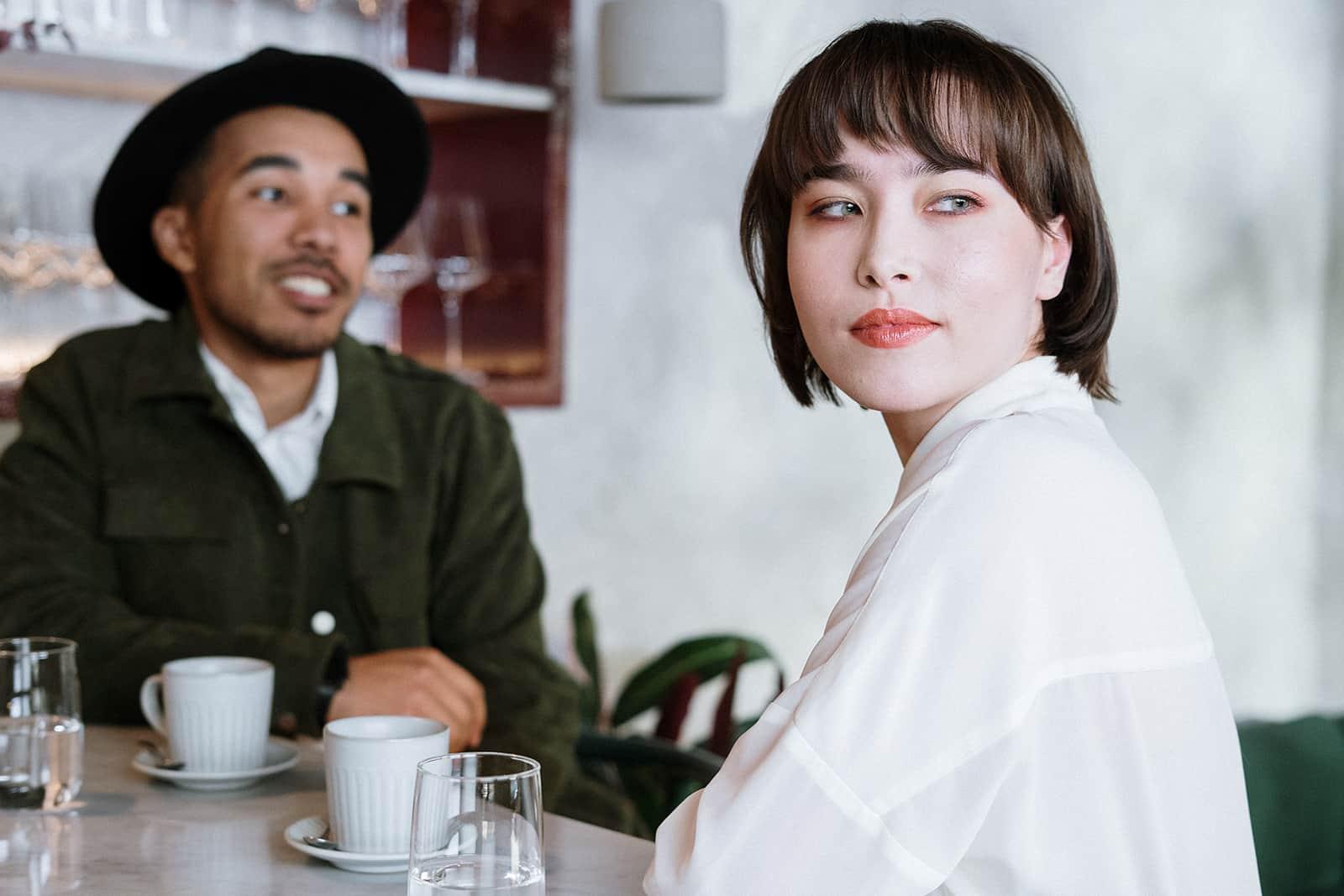 Une femme pensive tournant la tête d'un homme qui lui parle tout en buvant du café ensemble