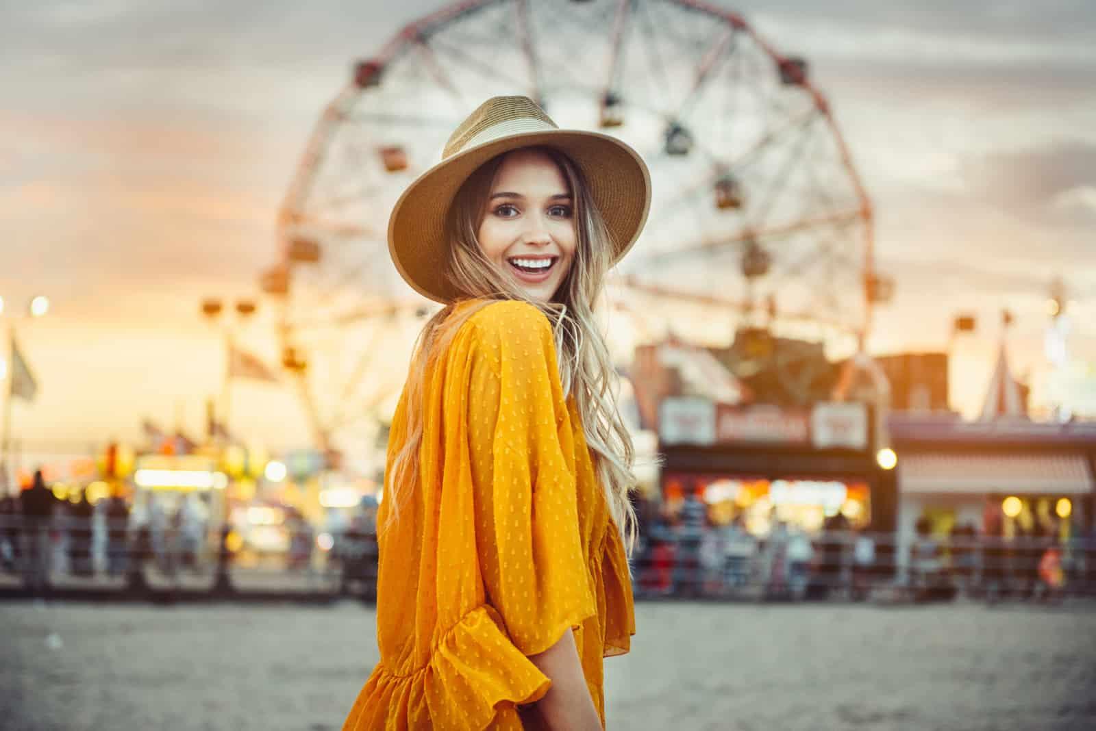 une femme souriante avec un chapeau sur la tête se dresse dans la rue