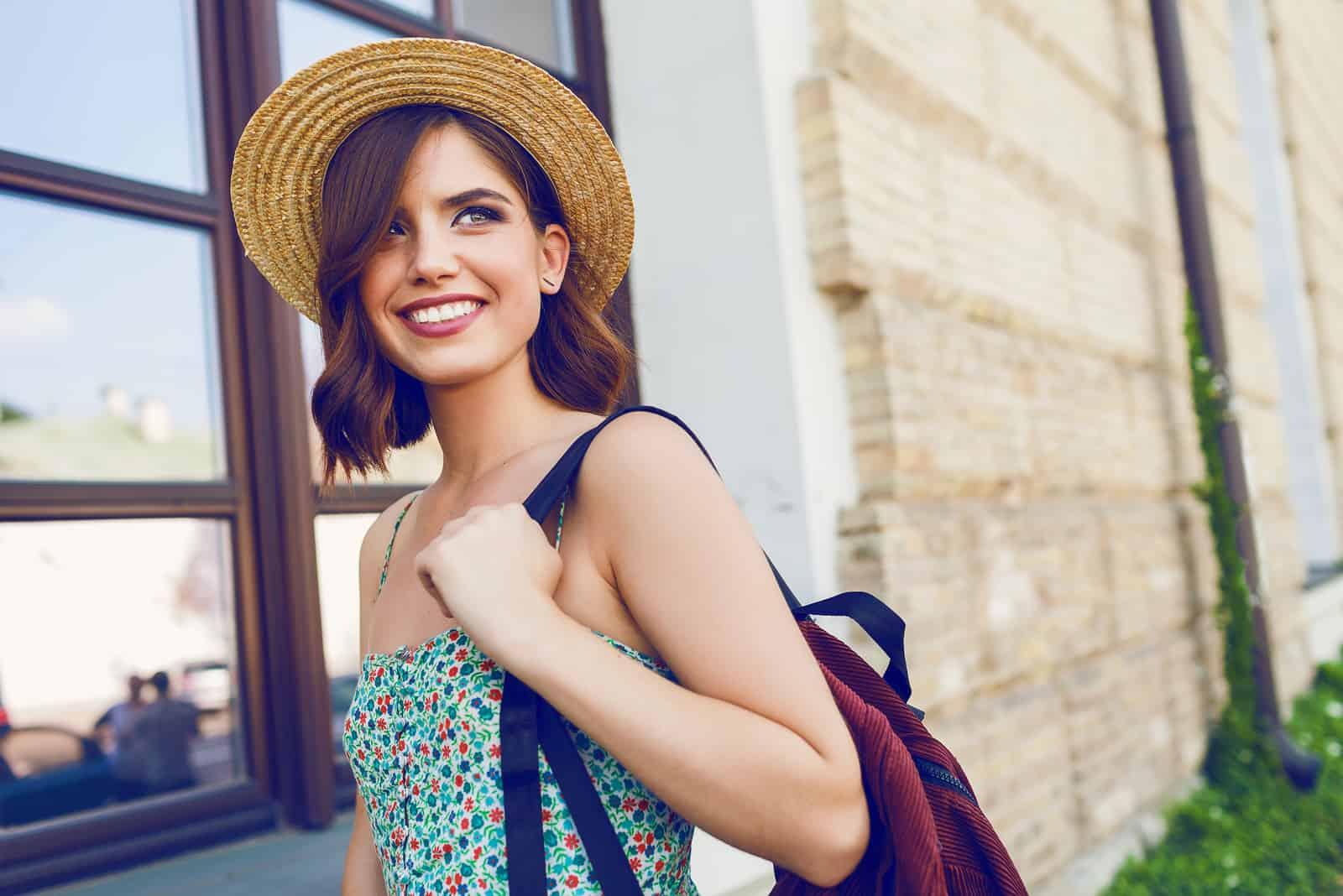 une femme souriante avec un chapeau sur la tête