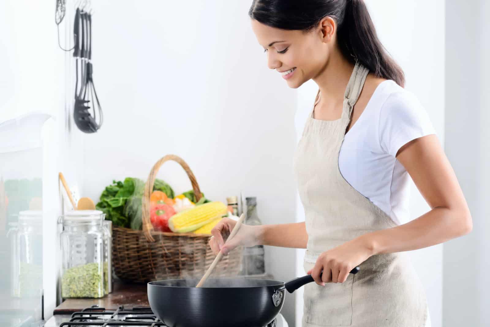 une femme souriante cuisine dans la cuisine