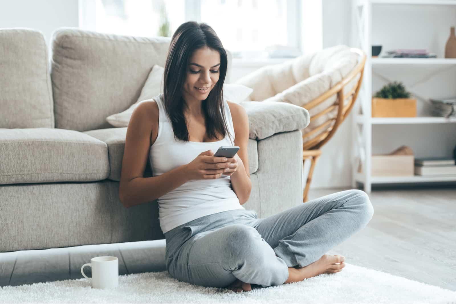 une femme souriante est assise sur le sol et les touches sur le téléphone