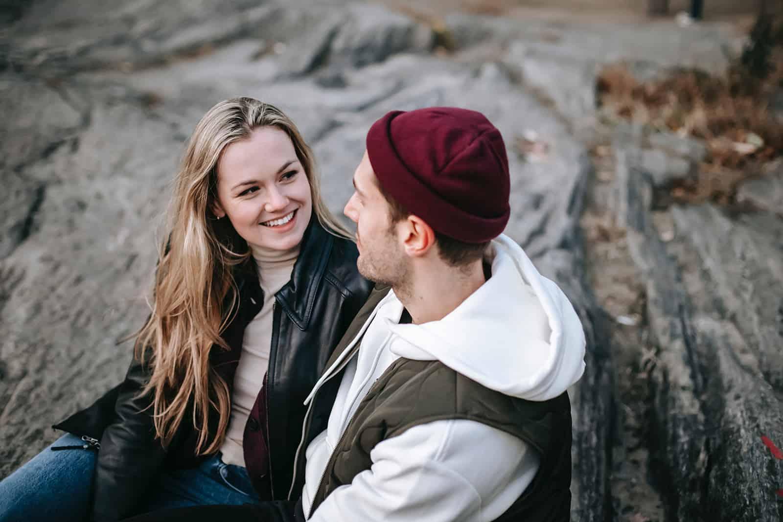 Une femme souriante regardant un homme assis près de la pierre ensemble