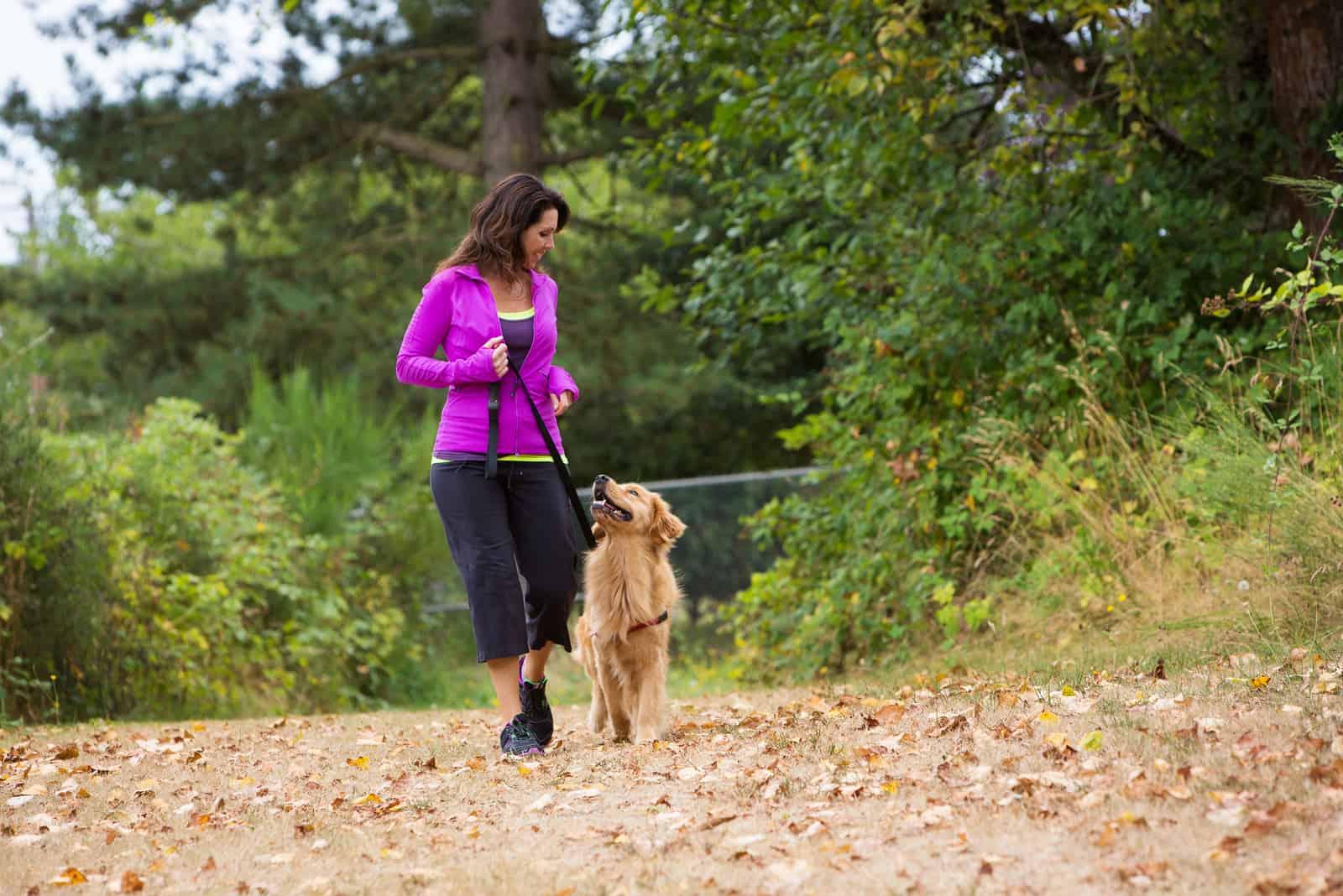 une femme souriante se dresse avec un chien