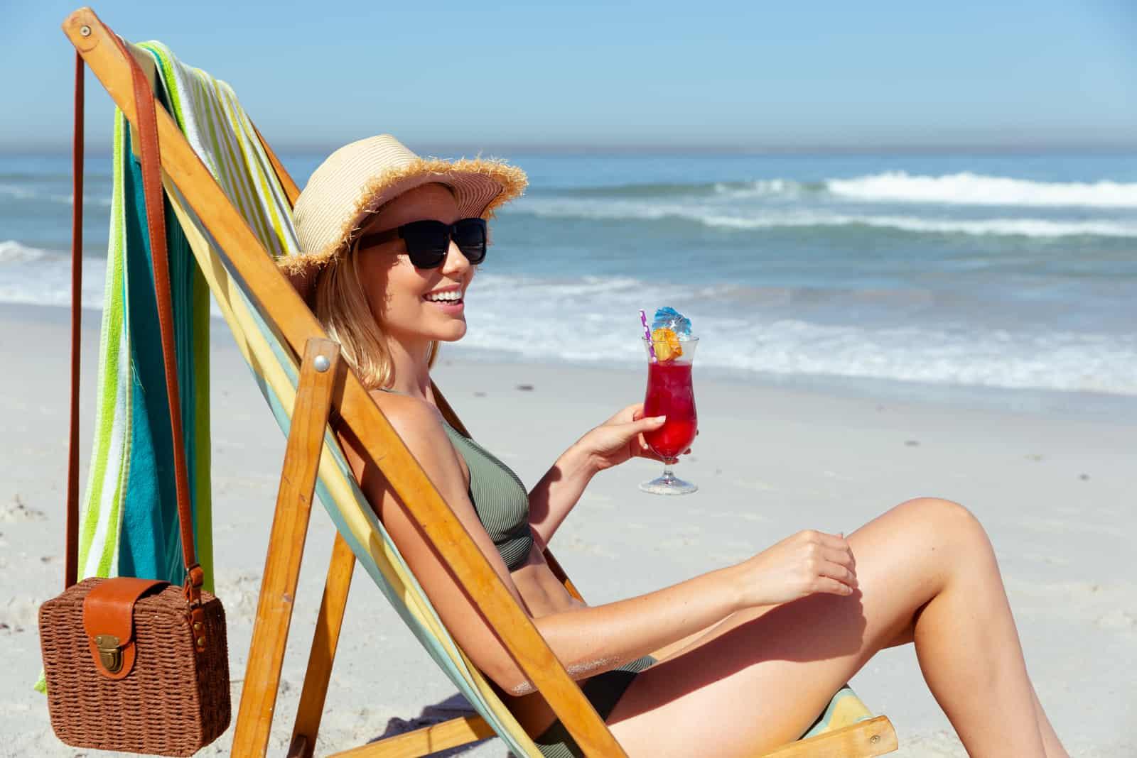 une femme souriante se trouve sur la plage et les bains de soleil