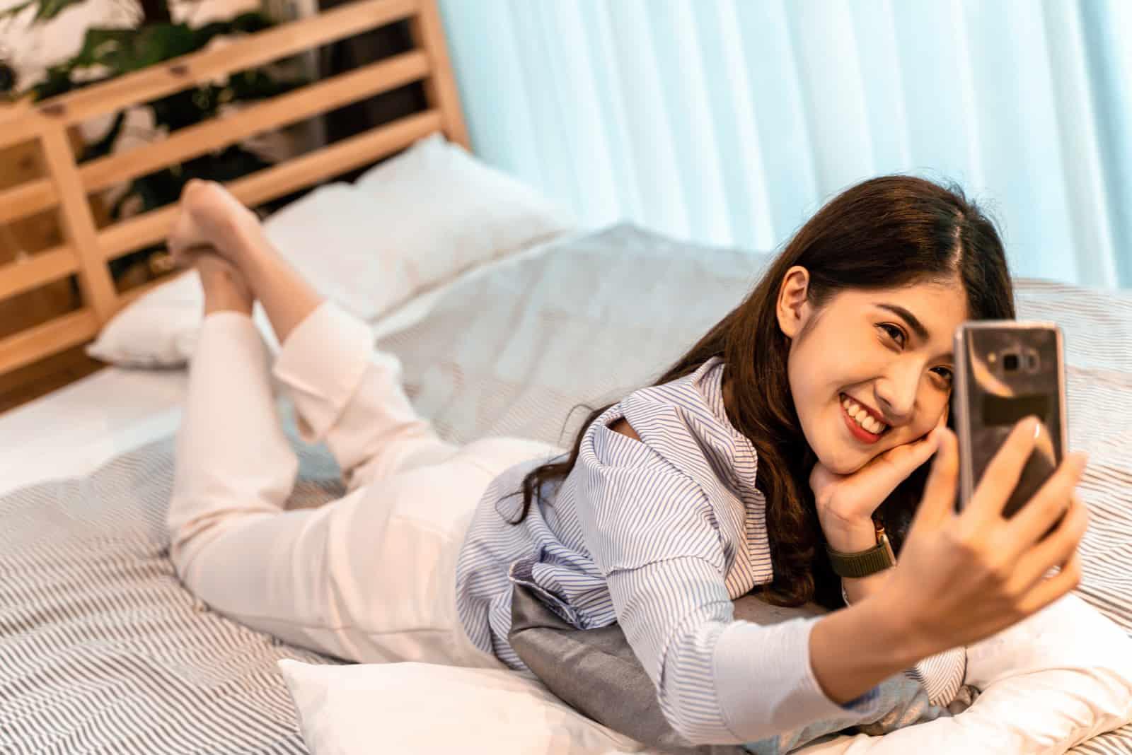 une femme souriante se trouve sur le lit et prend une photo