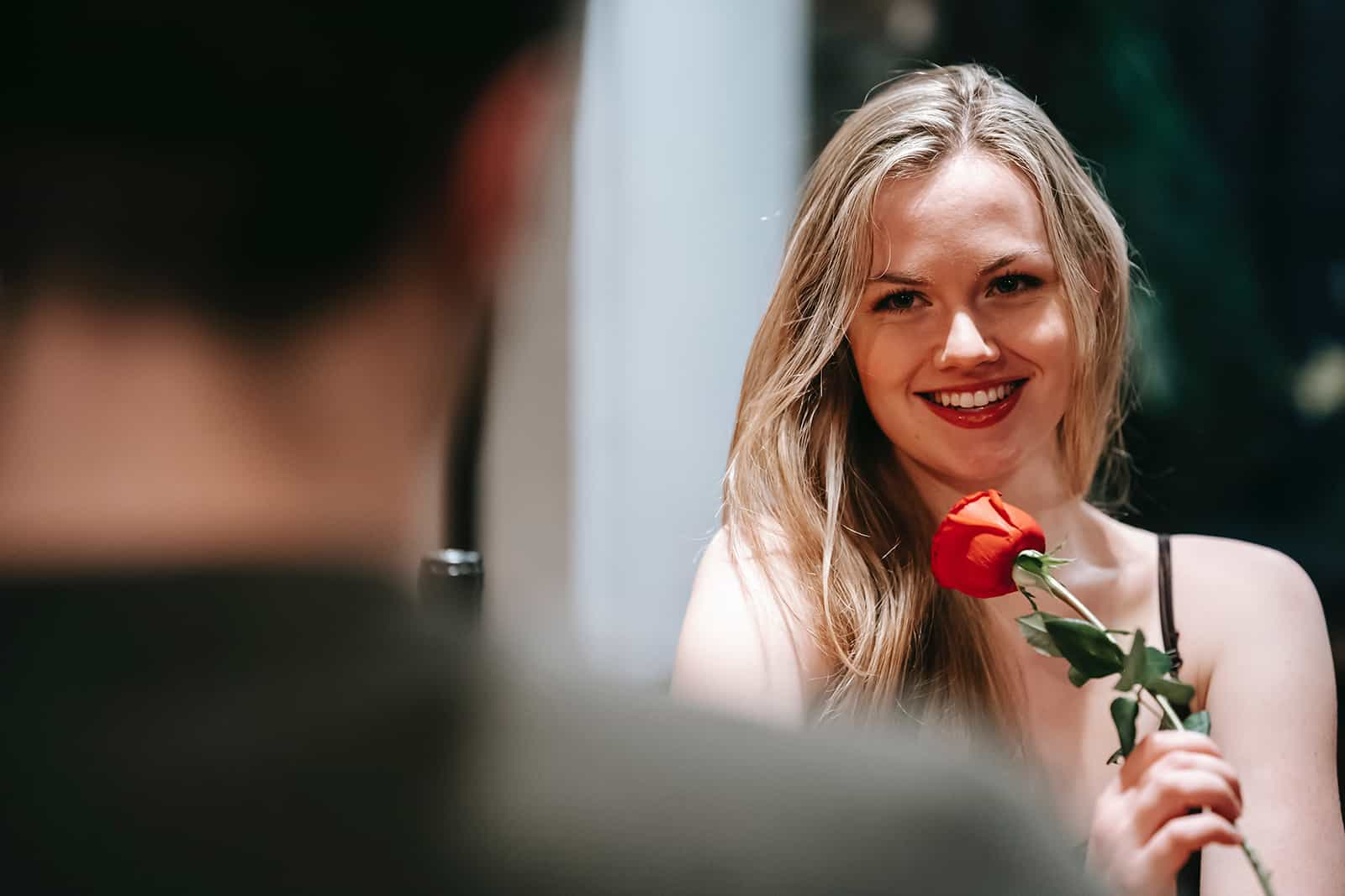 Une femme souriante tenant une rose rouge et regardant un homme assis en face d'elle