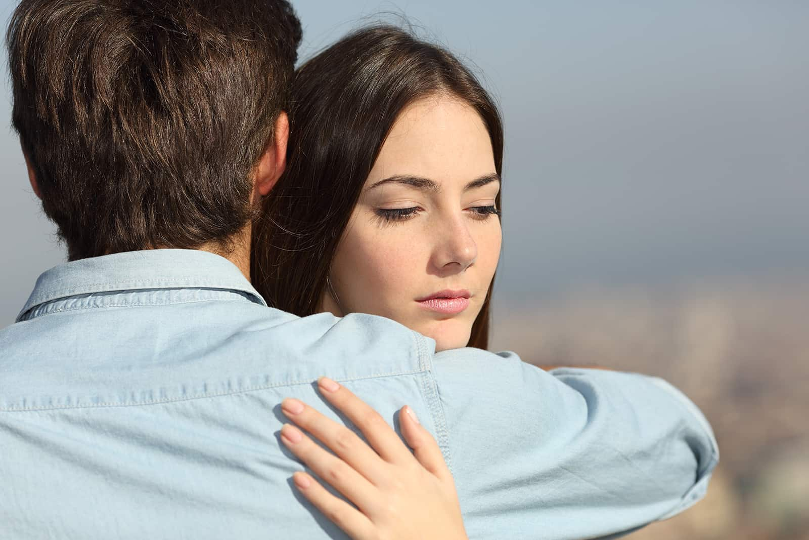 Une femme triste étreignant son petit ami et regardant vers le bas
