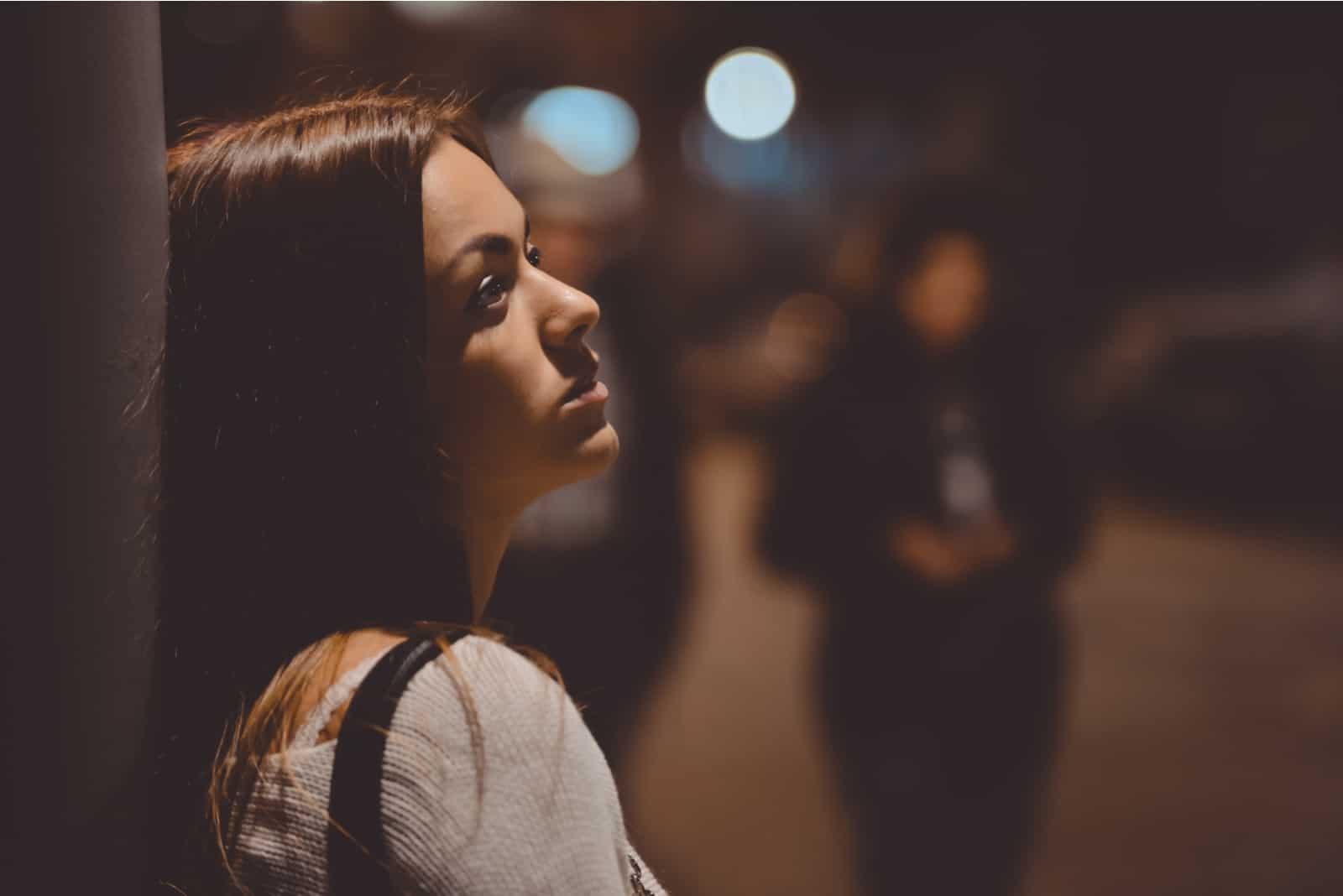 une jeune femme imaginaire se tient contre un mur