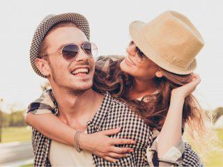 un homme souriant porte une femme pendant qu'elle le regarde et sourit