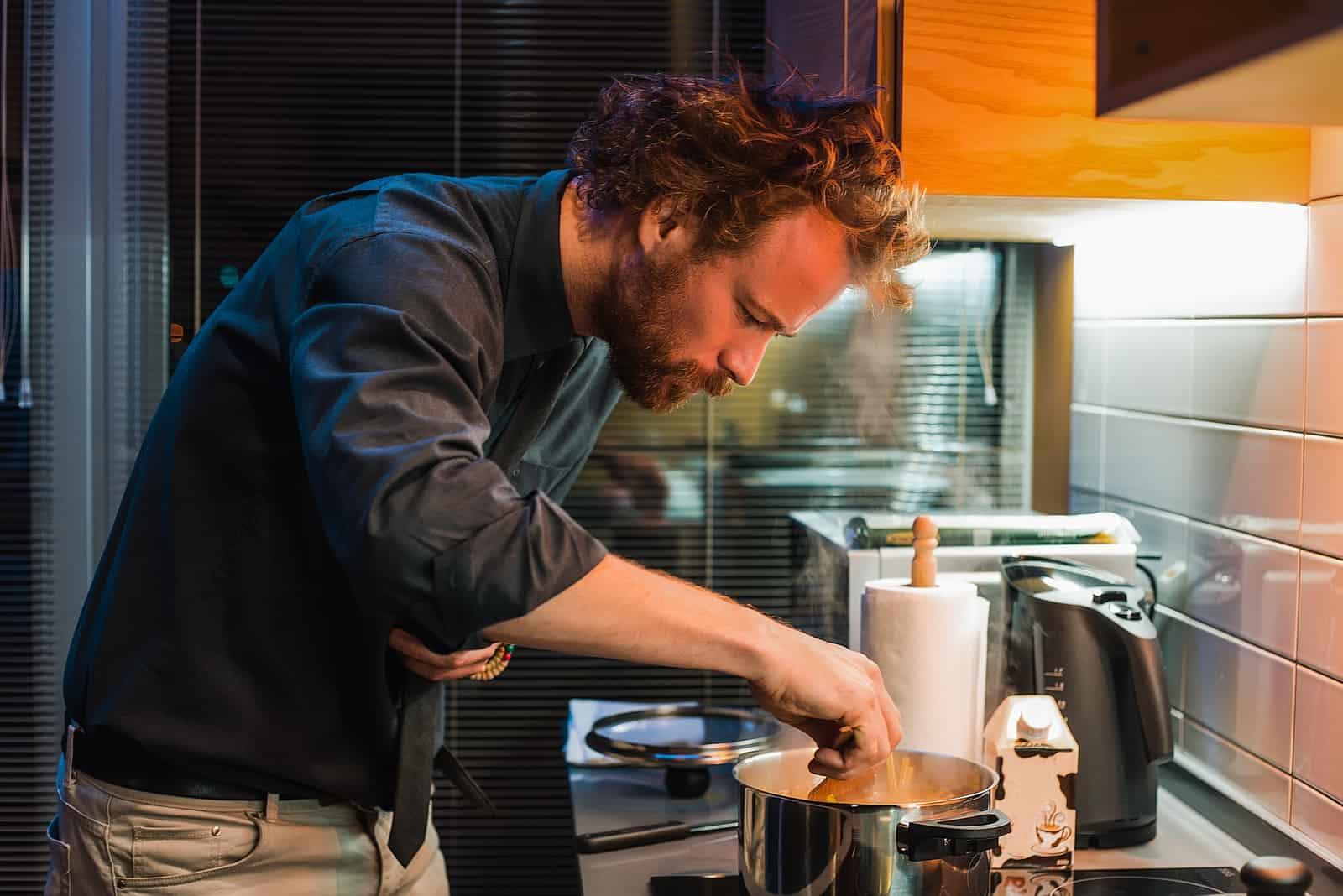 Bel homme cuisine dans la cuisine
