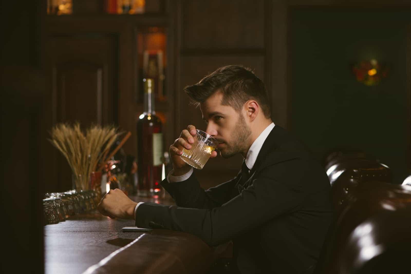Bel homme vêtu d'un smoking noir dans un bar à whisky