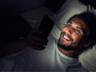 un homme souriant couché dans son lit et en appuyant sur un téléphone