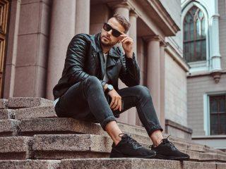 mec vêtu d'une veste noire et d'un jean