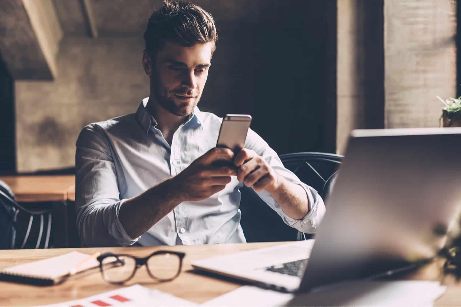 Confiant jeune homme en tenue décontractée intelligente tenant un téléphone intelligent