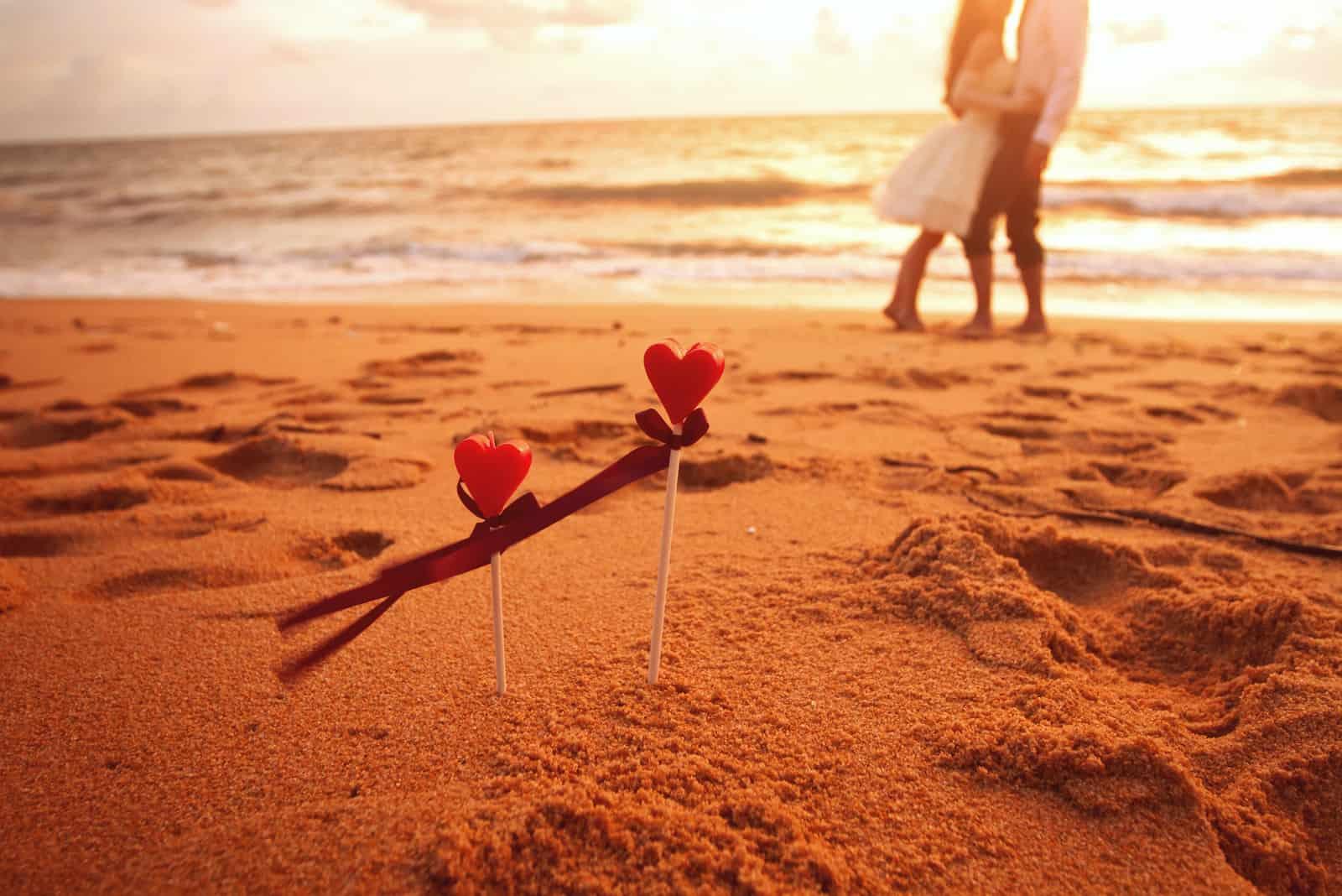 Couple d'amoureux debout sur la plage avec des coeurs sur des bâtons dans le sable