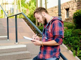 un homme se tient appuyé contre une clôture et écrit