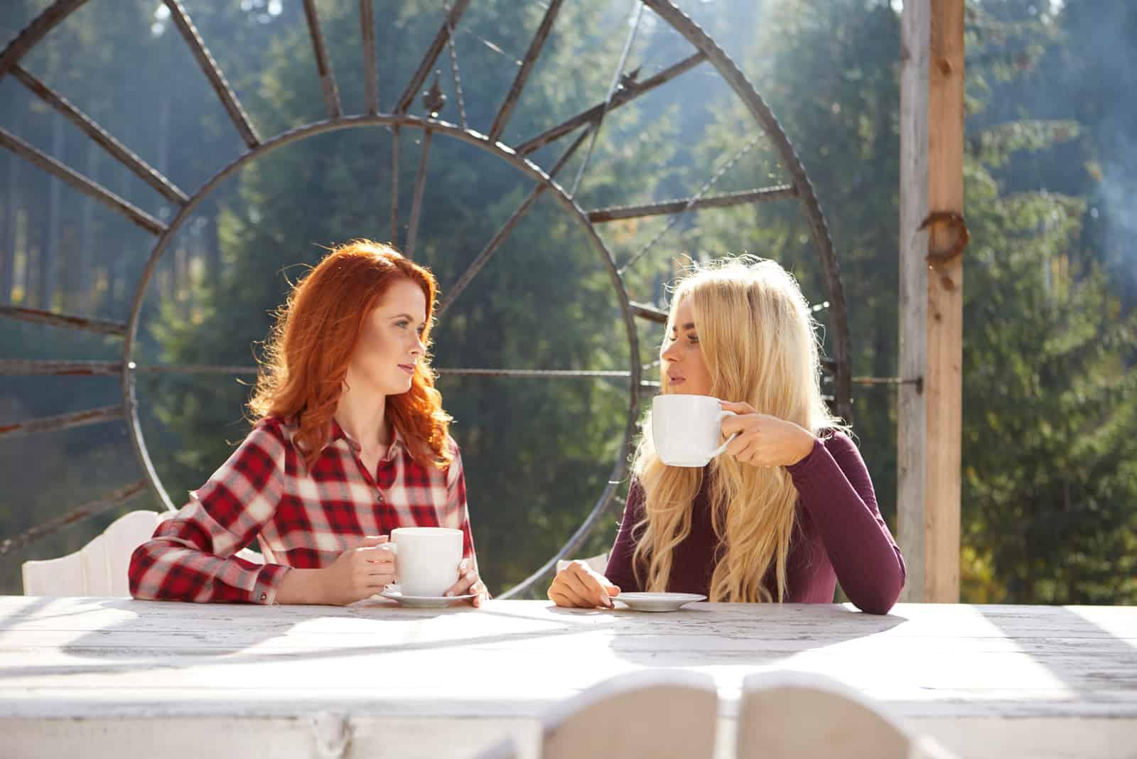 Deux amis heureux parlant à l'extérieur dans une terrasse de la maison