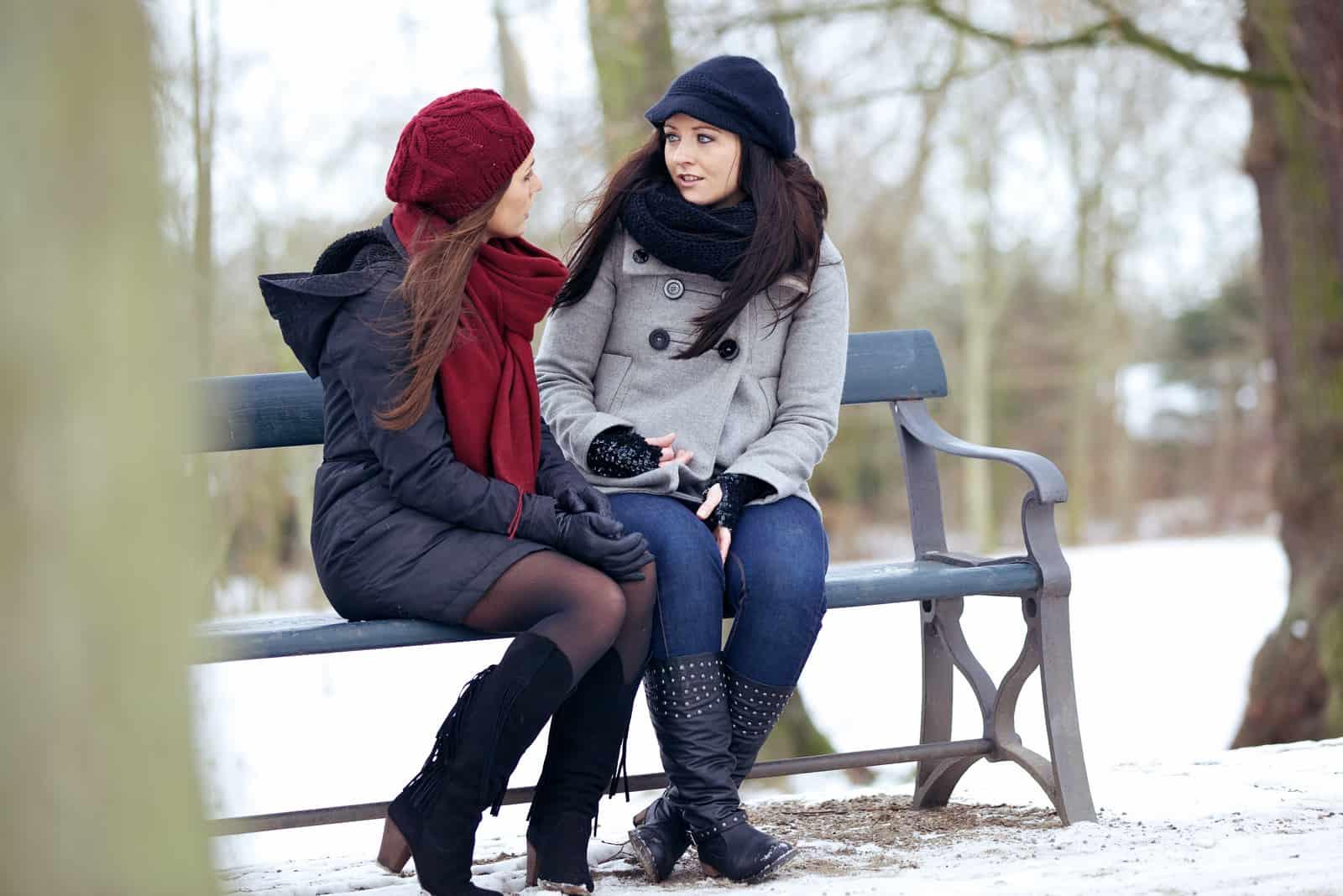 Deux meilleurs amis assis sur un banc de parc tout en ayant une conversation