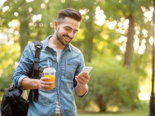 homme hipster marchant dans le parc automne et souriant