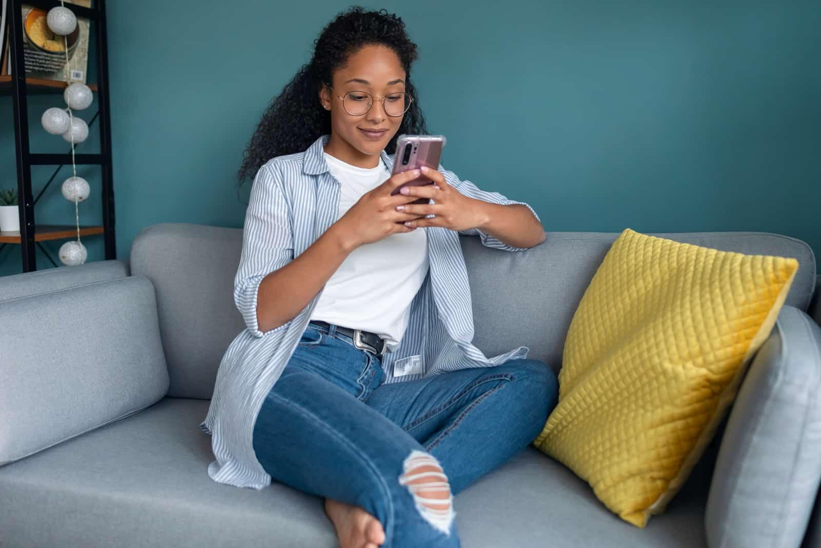 Femme à l'aide de son téléphone portable assis sur un canapé à la maison