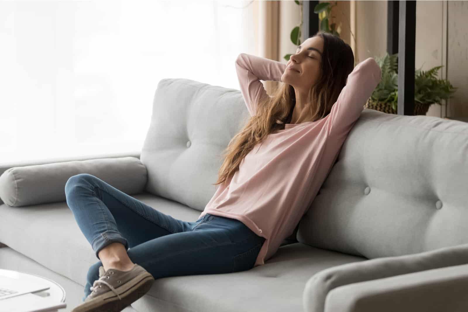 Femme assez reposante sur le canapé dans le salon