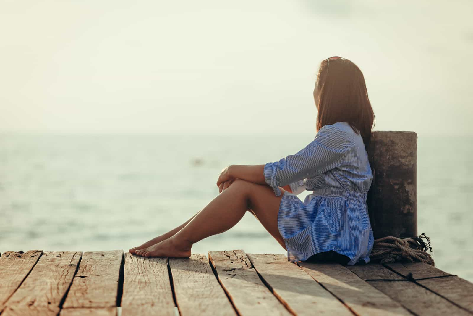 Femme assise seule solitaire sur un pont en bois