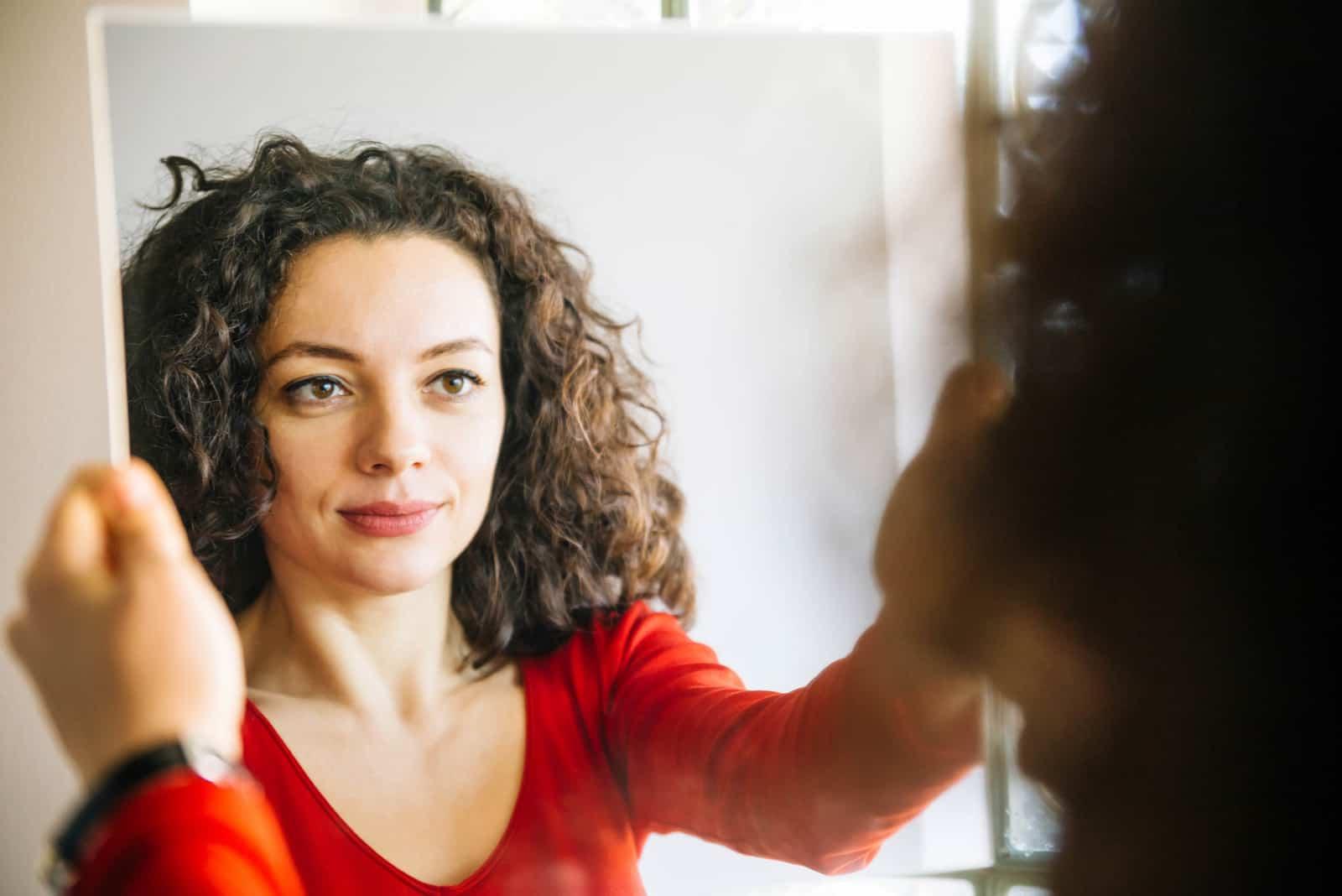 Femme aux cheveux bouclés, debout devant un grand miroir